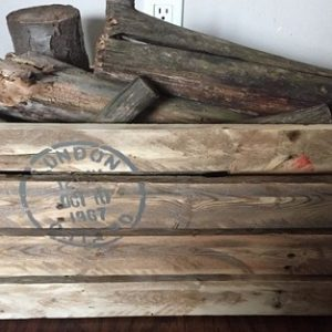 unpainted crate with London postal stamp stencil and rope handles, full of firewood and kindling
