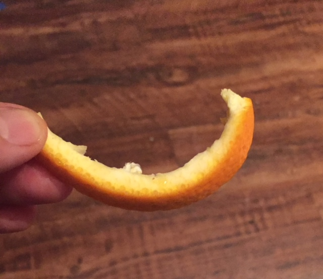 I'm holding a piece of thin orange rind, after the fruit was eaten off it