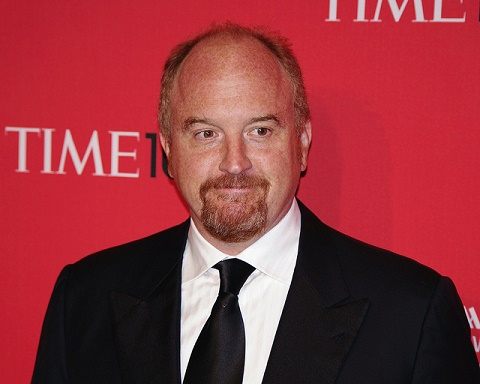 Louis CK with a half smile, in front of a Time Magazine backdrop
