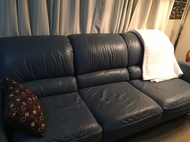 blue-grey couch with a brown/cream cushion on it and a cream throw